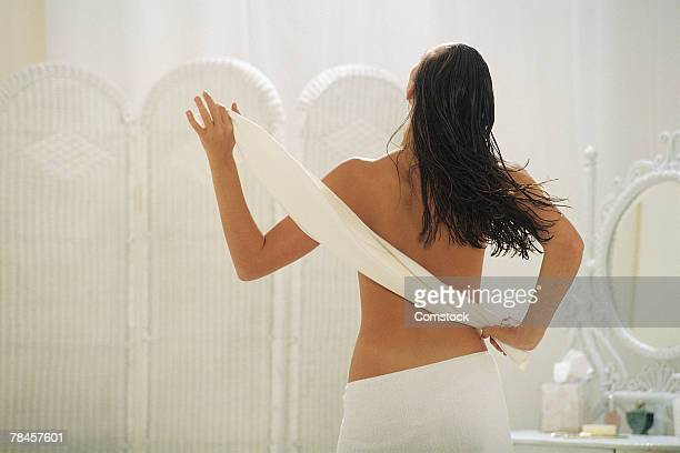Back view of woman drying off from bath
