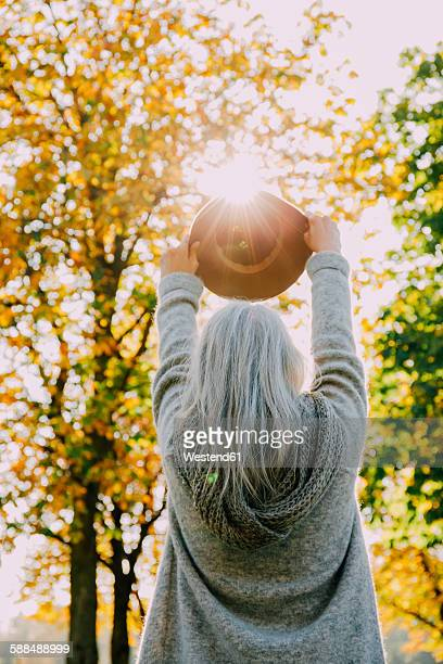 Back view of woman holding hat against the sun in an autumnal park