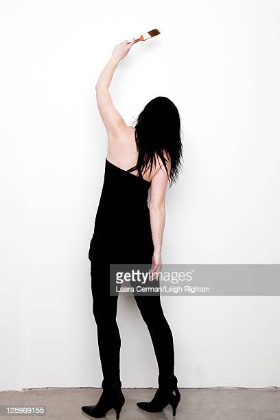 back view of woman (28 years old) in black dress painting wall - 25 29 years stock pictures, royalty-free photos & images