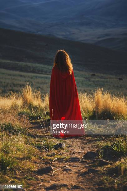 back view of woman in red cape walking down path through field toward shadowy valley at sunset - cape stock pictures, royalty-free photos & images