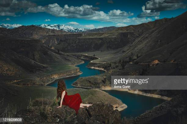back view of woman in red dress sitting overlooking dramatic river canyon and mountains - red dress stock pictures, royalty-free photos & images