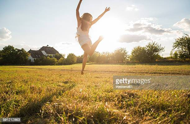 Back view of woman jumping in the air on a meadow at backlight