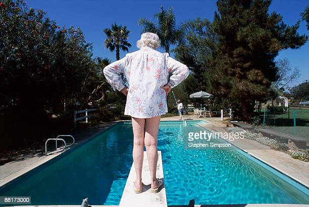 Back view of woman on diving board by pool