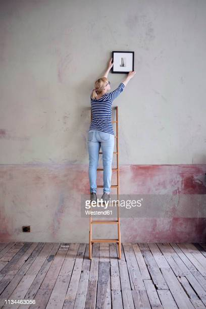 back view of woman on ladder hanging up picture frame in an unrenovated room of a loft - floorboard stock photos and pictures