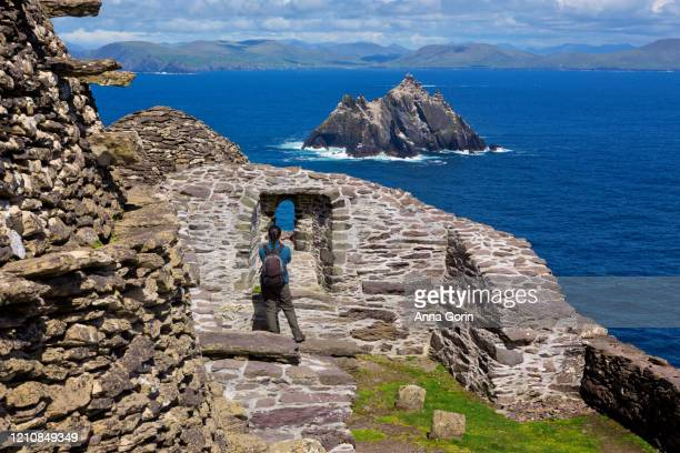 back view of woman pausing to take pictures through arch in ruins of skellig michael monasteries, county kerry, ireland - skellig michael ストックフォトと画像