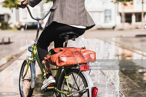 Back view of woman riding bicycle, partial view