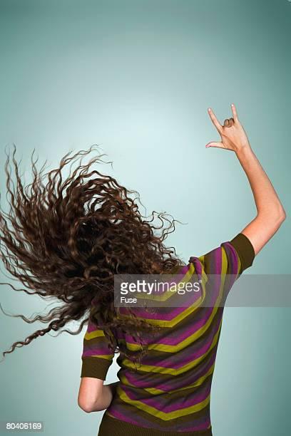 back view of woman rocking out - moderne rockmusik stock-fotos und bilder