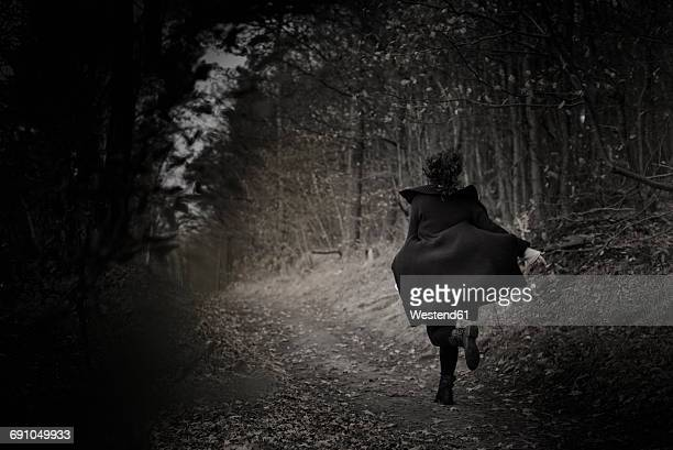 Back view of woman running on forest track