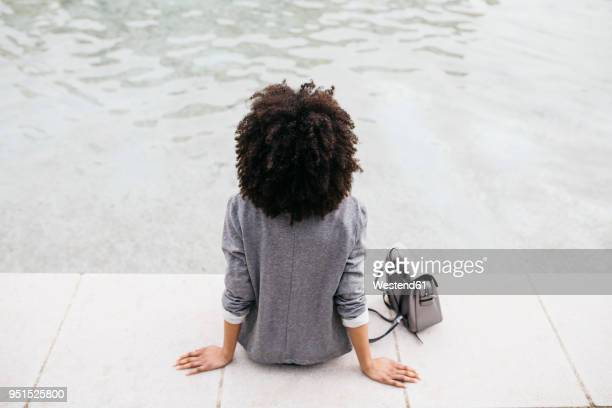 back view of woman sitting at edge of a pool - アフロ ストックフォトと画像
