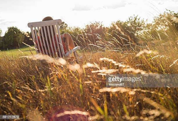Back view of woman sitting on a deck chair on a meadow