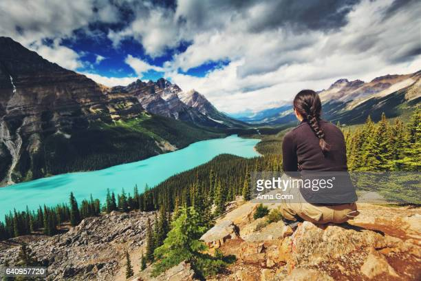 Back view of woman sitting on rocks overlooking Peyto Lake surrounded by mountains off Icefields Parkway, Canada, summer afternoon