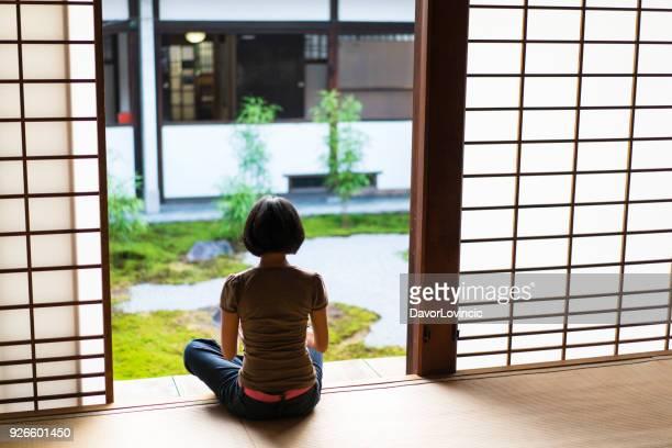 表彰台寺、京都の知恩寺禅庭で meditatimg に座っている女性の背面図 - 胡坐 ストックフォトと画像