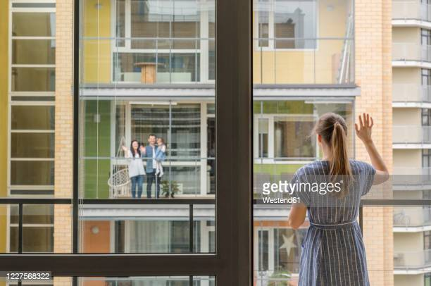 back view of woman standing on balcony waving to her neighbours - balcony stock pictures, royalty-free photos & images