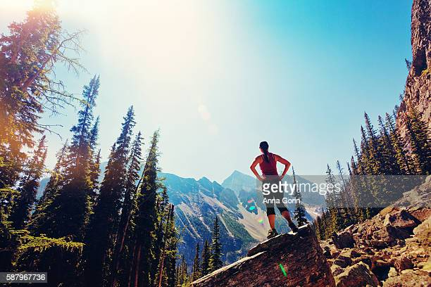 back view of woman standing on rocks with hands on hips, looking at canadian rockies, lens flare and vintage toning - hand on hip stock pictures, royalty-free photos & images