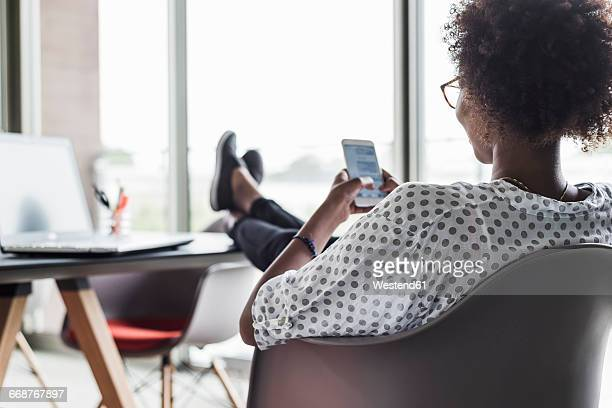 Back view of woman text messaging