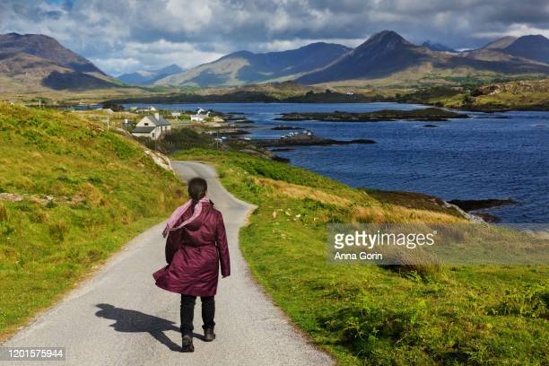 back view of woman walking down narrow road toward letterfrack town in connemara national park, stormy spring evening in western ireland, county galway - galway stock pictures, royalty-free photos & images