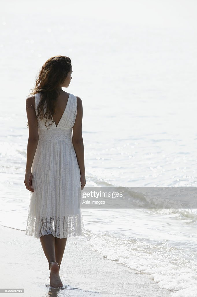 Back View Of Woman Wearing A White Dress And Walking A ...