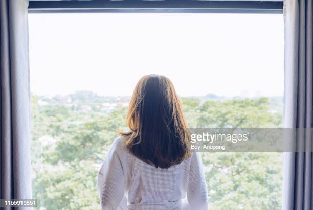 back view of woman wearing bathrobe, standing nearly window after waking up in the morning. - bathrobe stock pictures, royalty-free photos & images