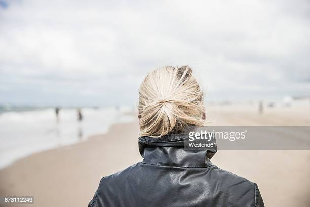 Back view of woman wearing leather jacket on the beach