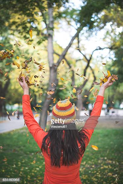 Back view of woman wearing woolly hat throwing autumn leaves in the air