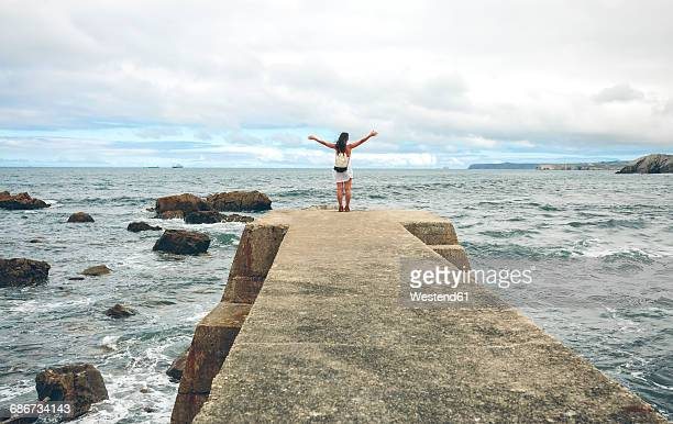 Back view of woman with arms outstretched standing on pier