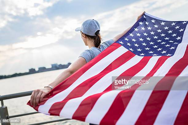 Back view of woman with basecap holding American Flag