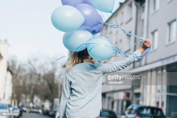 back view of woman with blue balloons - luftballon stock-fotos und bilder