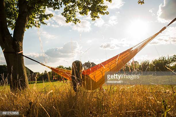 Back view of woman with headphones lying in a hammock relaxing in nature
