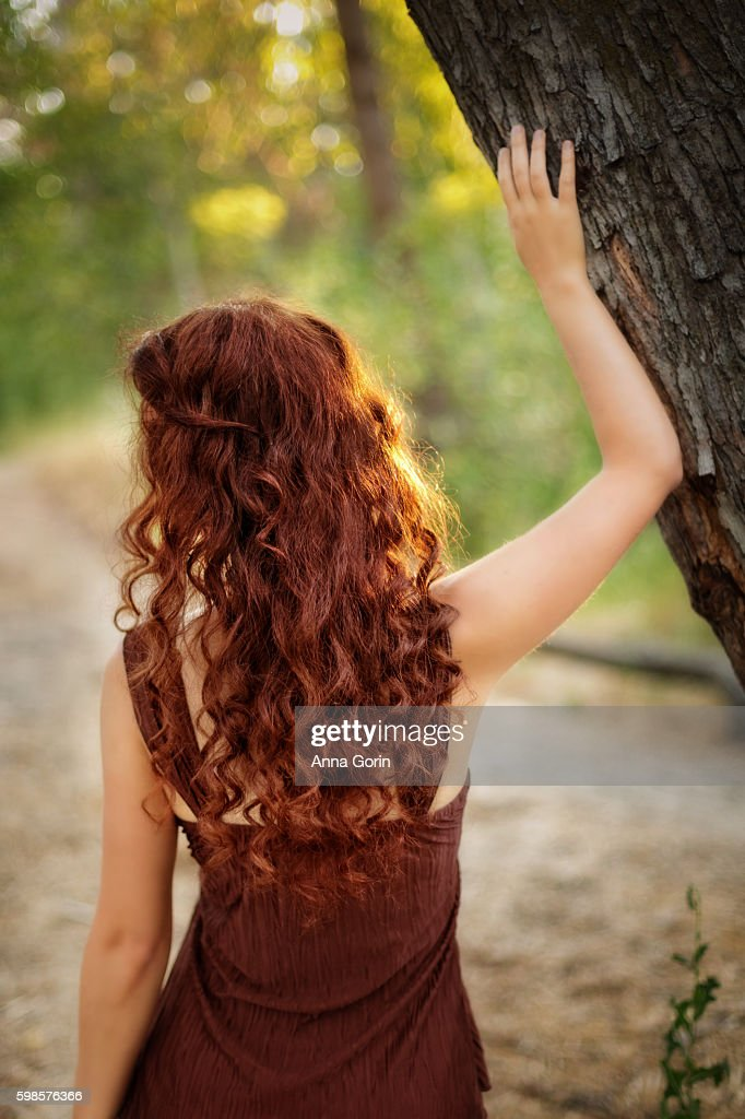 Back View Of Woman With Long Curly Red Hair In Forest Touching Tree