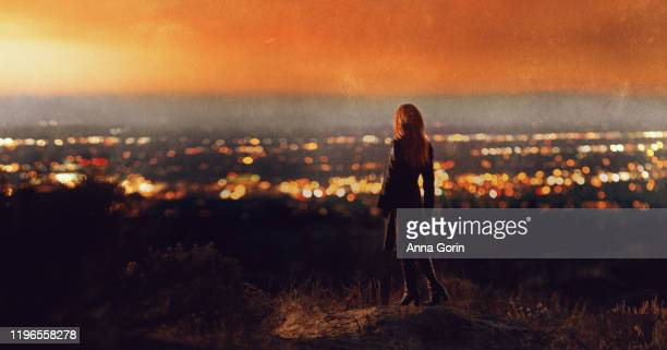 back view of woman with long red hair wearing black coat and heeled boots standing on hillside looking at sunset over valley of city lights - 見渡す ストックフォトと画像