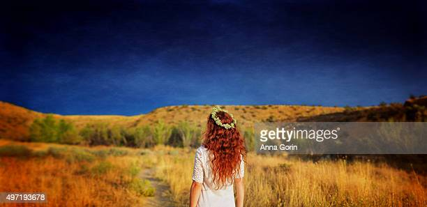 Back view of woman with long wavy red hair wearing flower crown looking at stormy sky over fields