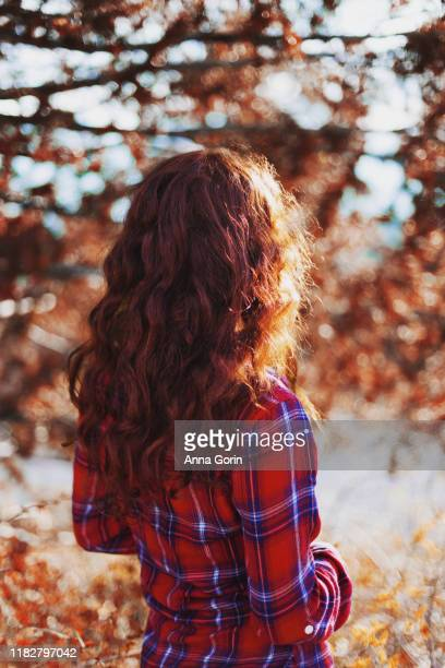 back view of woman with long wavy red hair wearing long-sleeved red plaid shirt, earth tones - capelli lunghi foto e immagini stock