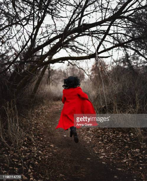 back view of woman with medium-length black hair in long red coat running down forest path in winter, desaturated effect - junge frau rätsel stock-fotos und bilder