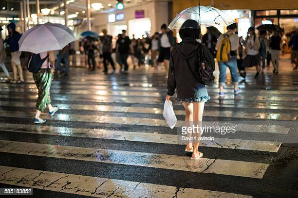 Back view of woman with umbrella on street in Kyoto.