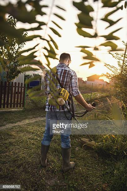 Back view of worker mowing the lawn with weed trimmer.