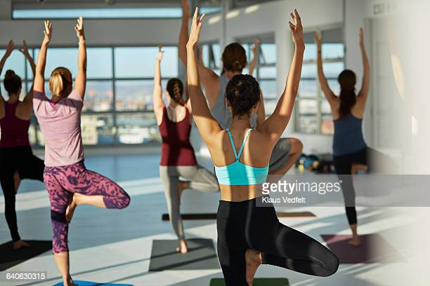 Back view of yoga class with stretched arms