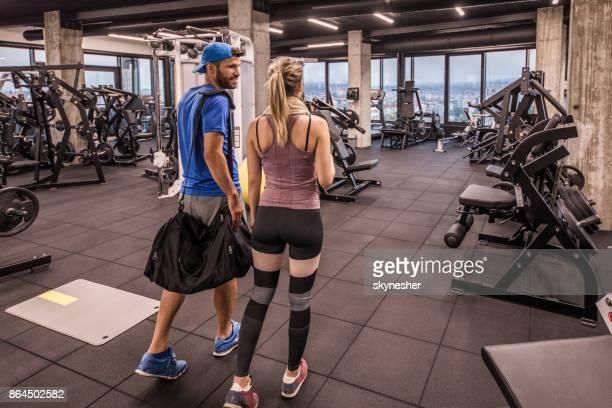 Vue arrière du jeune couple athlétique entrant dans la salle de gym et de communiquer.