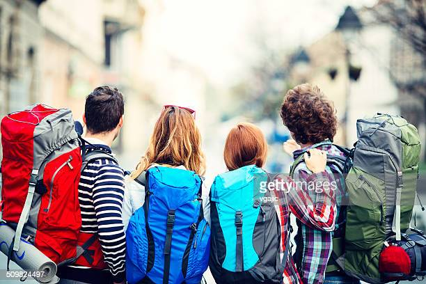 Back view of young backpackers in the city.