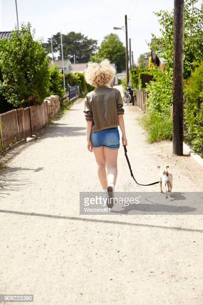 Back view of young blond woman going walkies with her dog