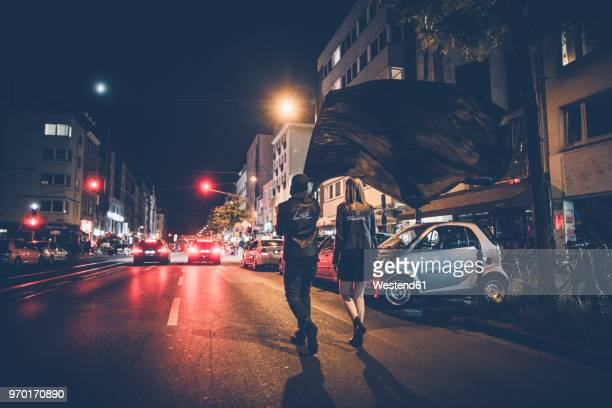 back view of young couple with black flag walking on the street by night - sociale rechtvaardigheid stockfoto's en -beelden