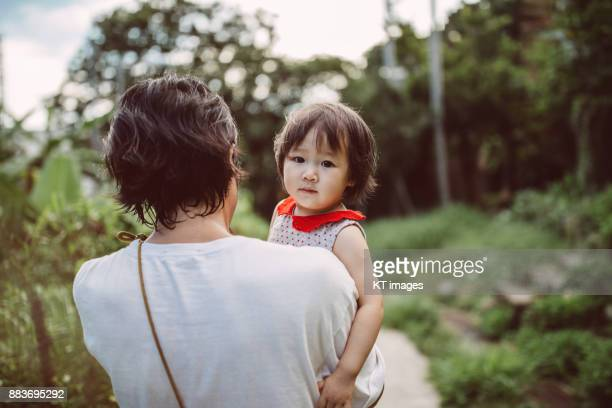 Back view of young father holding little daughter strolling along a pathway.