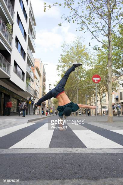 back view of young man doing handstand on zebra crossing - animated zebra stock pictures, royalty-free photos & images