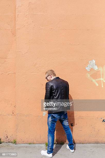 back view of young man peeing at facade - urinating stock pictures, royalty-free photos & images