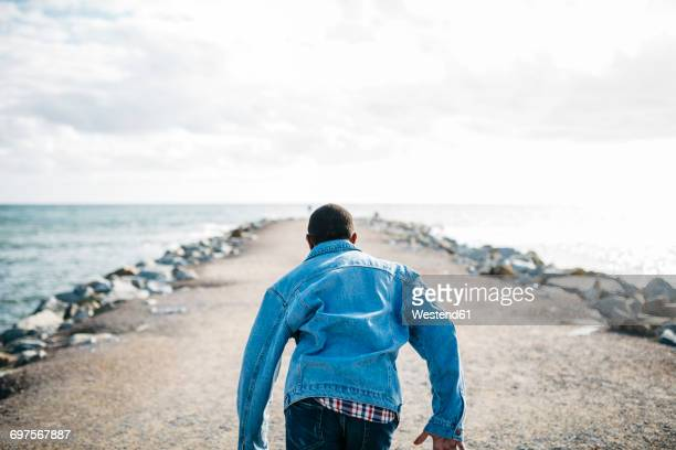 back view of young man running on jetty - denim jacket stock pictures, royalty-free photos & images