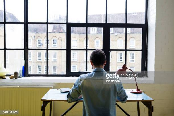 Back view of young man sitting at desk in his loft working with laptop