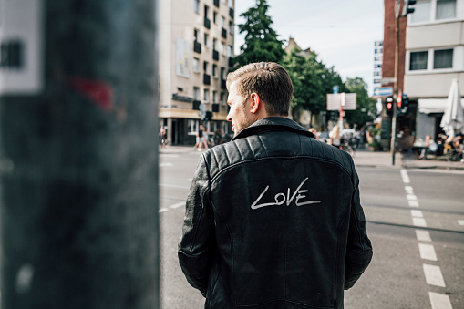 Back view of young man wearing black leather jacket with writing 'Love' - gettyimageskorea