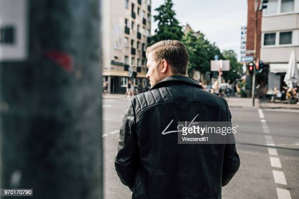 back view of young man wearing black leather jacket with writing 'love' - jaqueta - fotografias e filmes do acervo