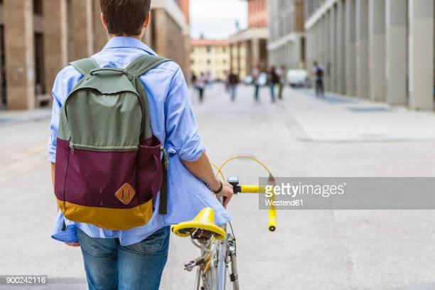 Back view of young man with backpack pushing his bike