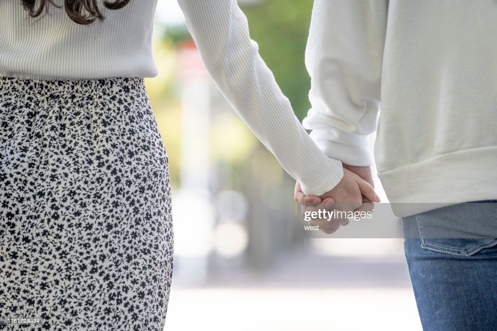 Back view of young men and women who hold hands together : Stock Photo