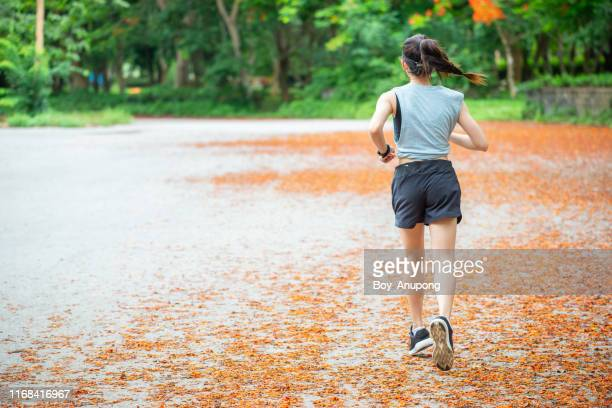 back view of young runner woman running in the park. - joggeuse photos et images de collection